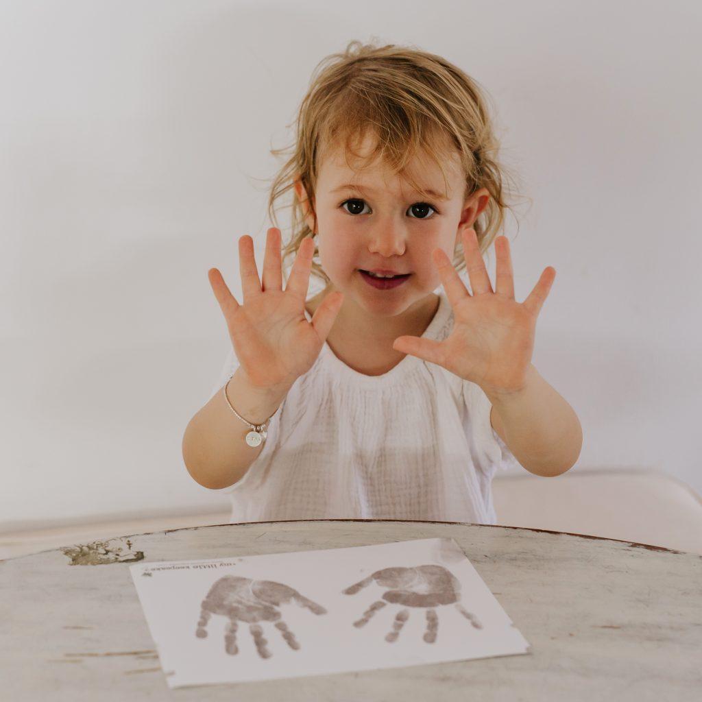Little girl doing inkless handprint